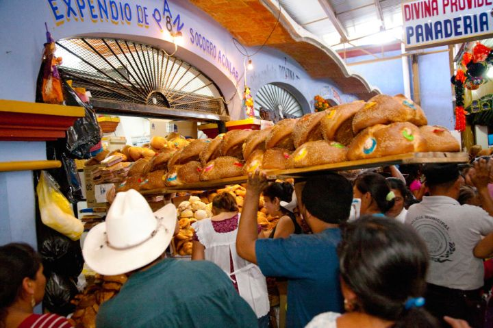 Man delivering special bread, pan de muertos, in crowded market during annual Day of the Dead celebration, Ocotlan, Mexico